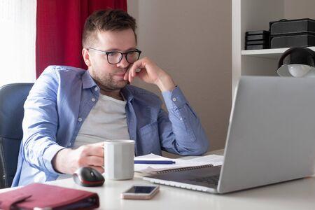 Caucasian man working at home on laptop computer Zdjęcie Seryjne