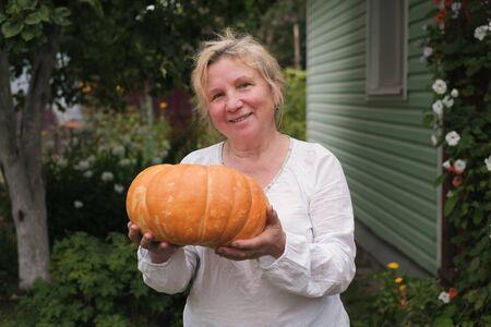 Senior caucasian woman collecting vegetables at her garden.