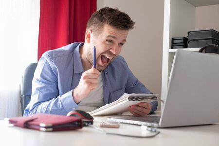 young caucasian man working on laptop being excited with results of his strat up.