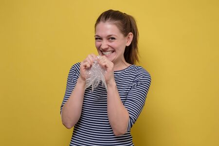 Laughing woman bursts bubbles on a packaging wrap, calming down Imagens