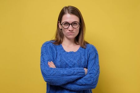 Young angry woman in blue sweater folded her arms