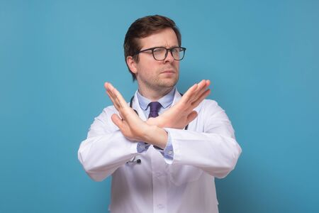 doctor making cross with hands over chest, showing stop and prohibition gesture, Stock fotó