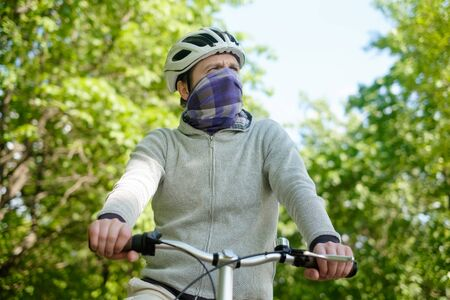 Young cauacasian man in helmet cycling outdoor in forest closing his face with scarf
