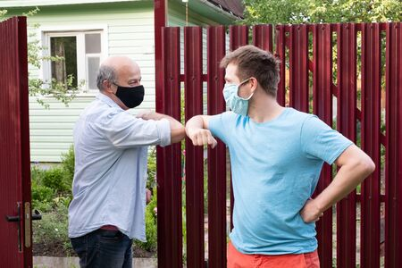 Two men in medical mask greeting each other with elbows on sunny day