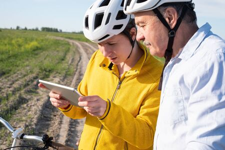 Father and daughter cycling outdoors looking for right route