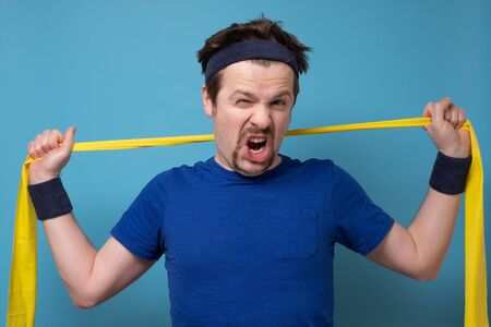 athletic man exercising with rubber band on blue wall.