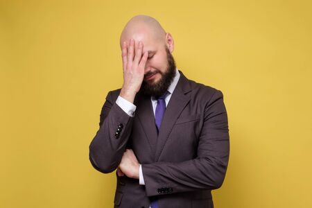 Thoughtful tired mature man trying to concentrate, or suffering from headache, standing over yellow background Standard-Bild