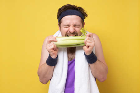 Sportive caucasian young man biting a celery on yellow background. I love vegetables so much.