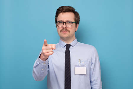 Young business man seriously pointing at you