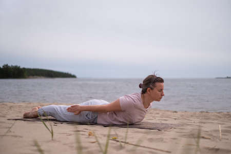 Caucasian woman practicing yoga, doing Salabhasana pose variation on beach