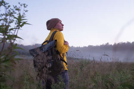 Caucasian woman walking in field alone. Girl in sport clothes hiking with backpack.