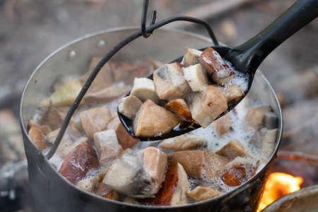 Kettle full of mushrooms on the fire