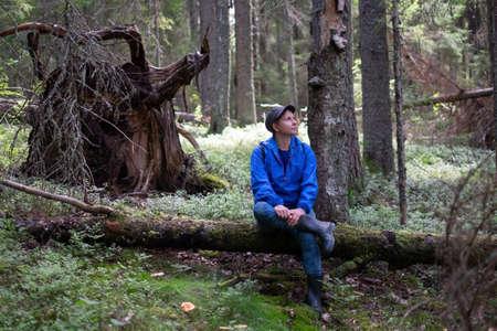Traveler sitting on fallen tree in woods resting.