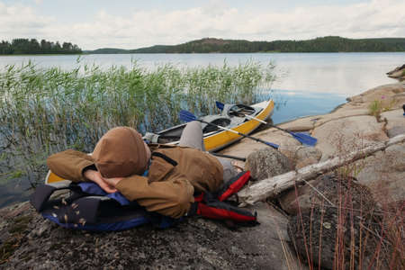 Man resting on the beach after canoeing.
