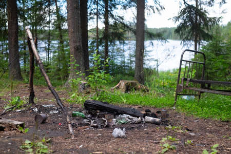 Garbage and fireplace in the forest near lake.