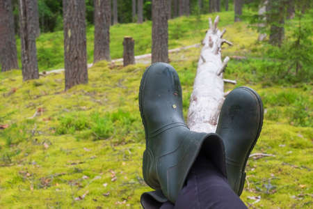 Resting on the fallen tree at the forest. Rubber boots on the nature Zdjęcie Seryjne