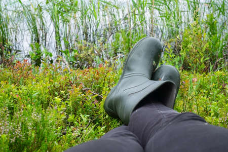 Man in rubber boots resting on moss near lake.