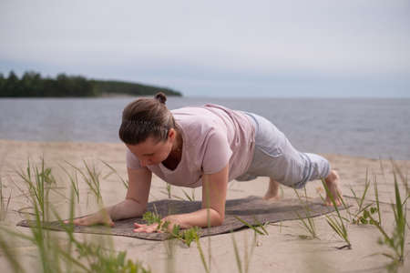 Young woman doing plank position outside on the beach.