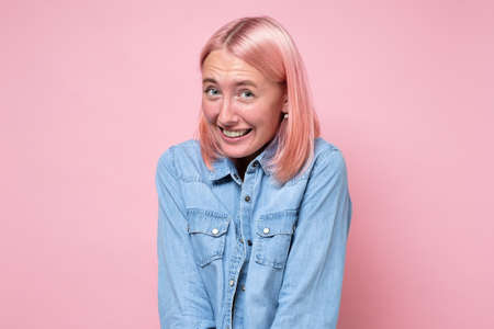 Woman with pink dyed hair smiling looking shy at camera