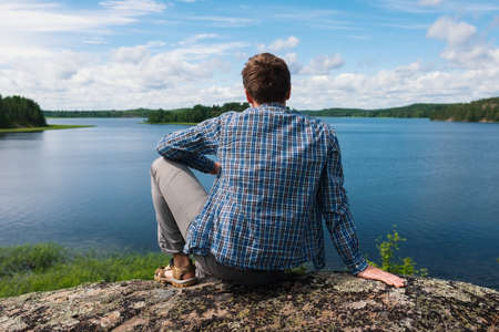 Man sitting on a hill looking on water of lake.