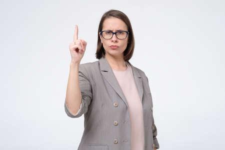 Mature woman raising her finger up warningly. Banco de Imagens