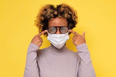 African american woman with foggy glasses caused by wearing a COVID protective mask Standard-Bild