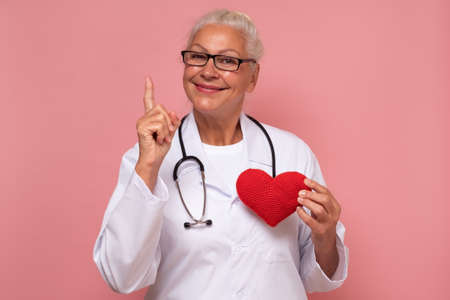 Female senior doctor holding a red heart encouraging a healthy lifestyle