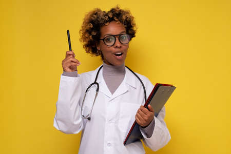 Young female african american doctor pointing finger upwards giving advice. Reklamní fotografie