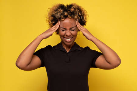 African woman with a headache holding hands on head, isolated on yellow background