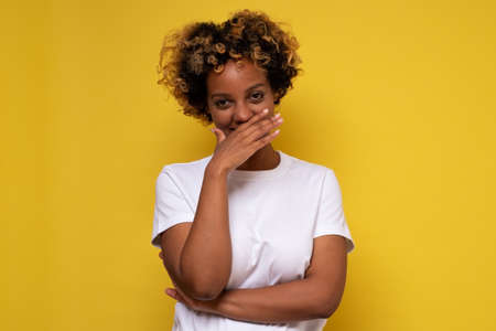 Young african woman giggles covering her mouth with hand, hiding her emotion Archivio Fotografico