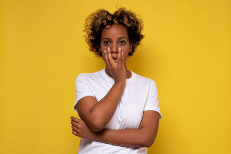 Lovely confused african woman with curly hair against yellow wall. Stock Photo