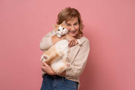 Mature woman lovingly hugging cat on pink wall.