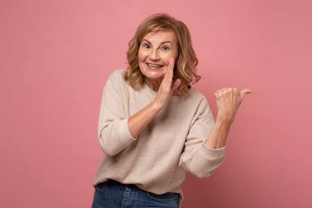 Beautiful middle age woman holding hand on mouth telling secret rumor