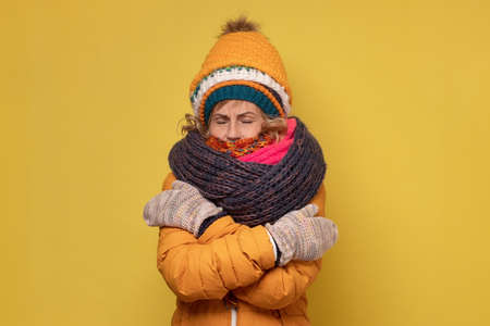 Winter portrait of funny mature woman wearing several caps and scarfs. Reklamní fotografie