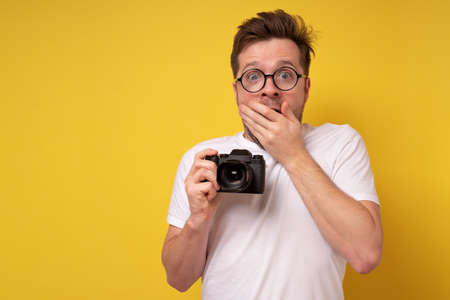 young man holding photocamera taking photo being shocked with results