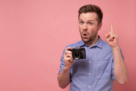 young man holding photocamera taking photo pointing with index finger up giving advice. Zdjęcie Seryjne