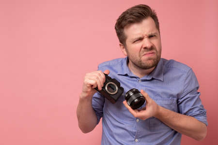 Traveler and photographer. Studio portrait of handsome young man holding photocamera taking photo. Yellow blackground.