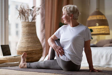 Senior caucasian woman in half spinal twist pose on mat