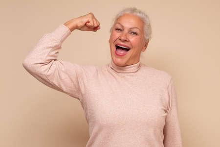 Elderly happy senior woman showing her muscles being self confident. Zdjęcie Seryjne - 157908106
