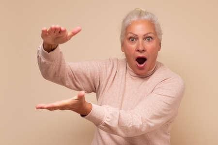 Amazed senior caucasian woman showing with hands large size feels shocked Zdjęcie Seryjne