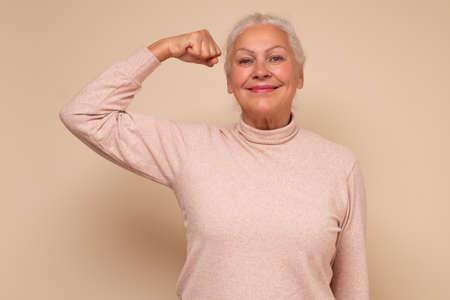 Elderly happy senior woman showing her muscles being self confident. Zdjęcie Seryjne