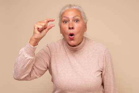 European senior woman showing something small in size with hands