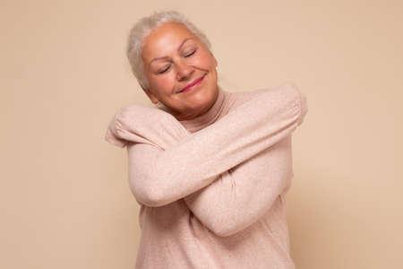 Positive relaxed senior woman closing eyes with pleasure, keeping arms around herself Zdjęcie Seryjne
