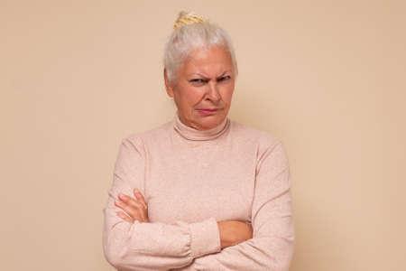 Suspicious elderly woman showing distrustful look at camera