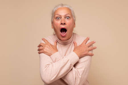 Frightened elderly woman looking surprised and shocked.