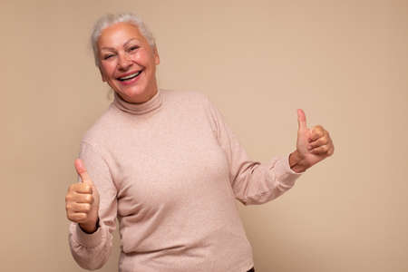 Happy senior woman showing her two thumbs up being happy making a choice