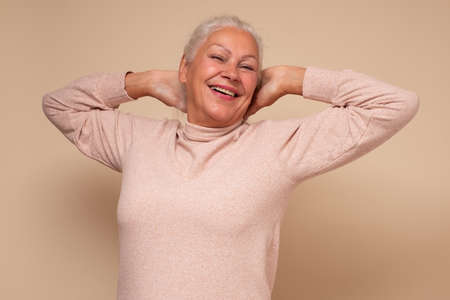 Excited senior woman raised stretched hands resting on weekend