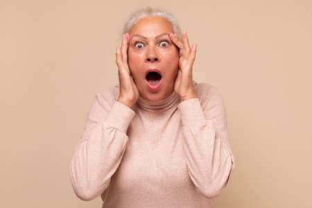 Amazed elderly woman looking surprised and shocked. Zdjęcie Seryjne