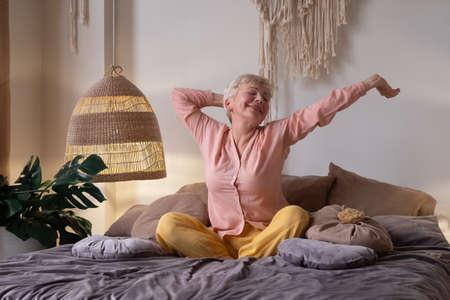senior woman wearing pyjama smiling in bright living room stretching waking up. Zdjęcie Seryjne