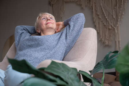 European woman resting , rejoicing at good positive news, sitting at home on couch Zdjęcie Seryjne